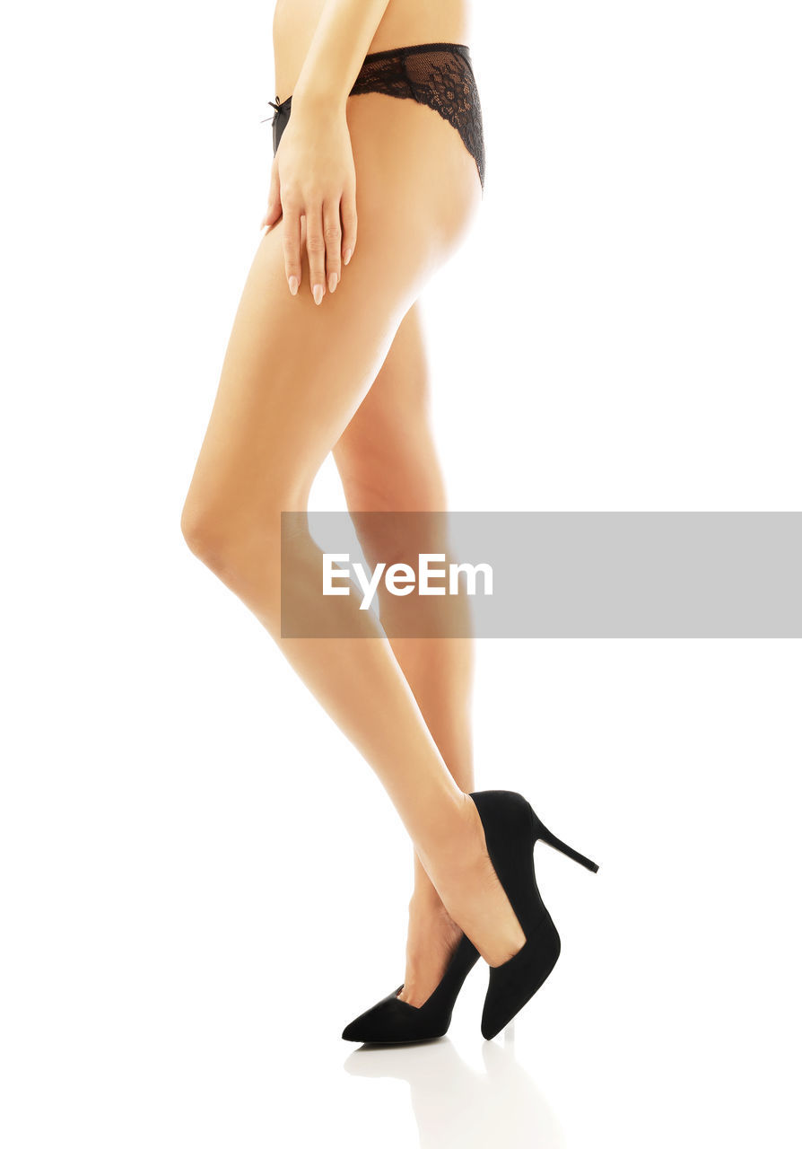 Low section of woman wearing black high heels and panties against white background