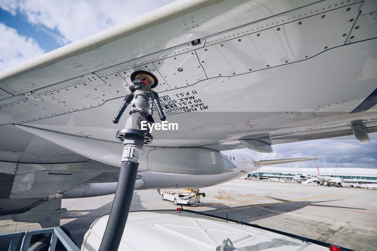 Airplane refueling at airport runway against sky