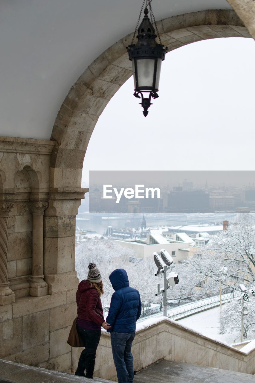architecture, built structure, two people, building exterior, city, winter, real people, adult, men, women, rear view, nature, sky, water, day, togetherness, cold temperature, cityscape, standing, arch, couple - relationship, warm clothing, outdoors, bridge - man made structure, looking at view, positive emotion
