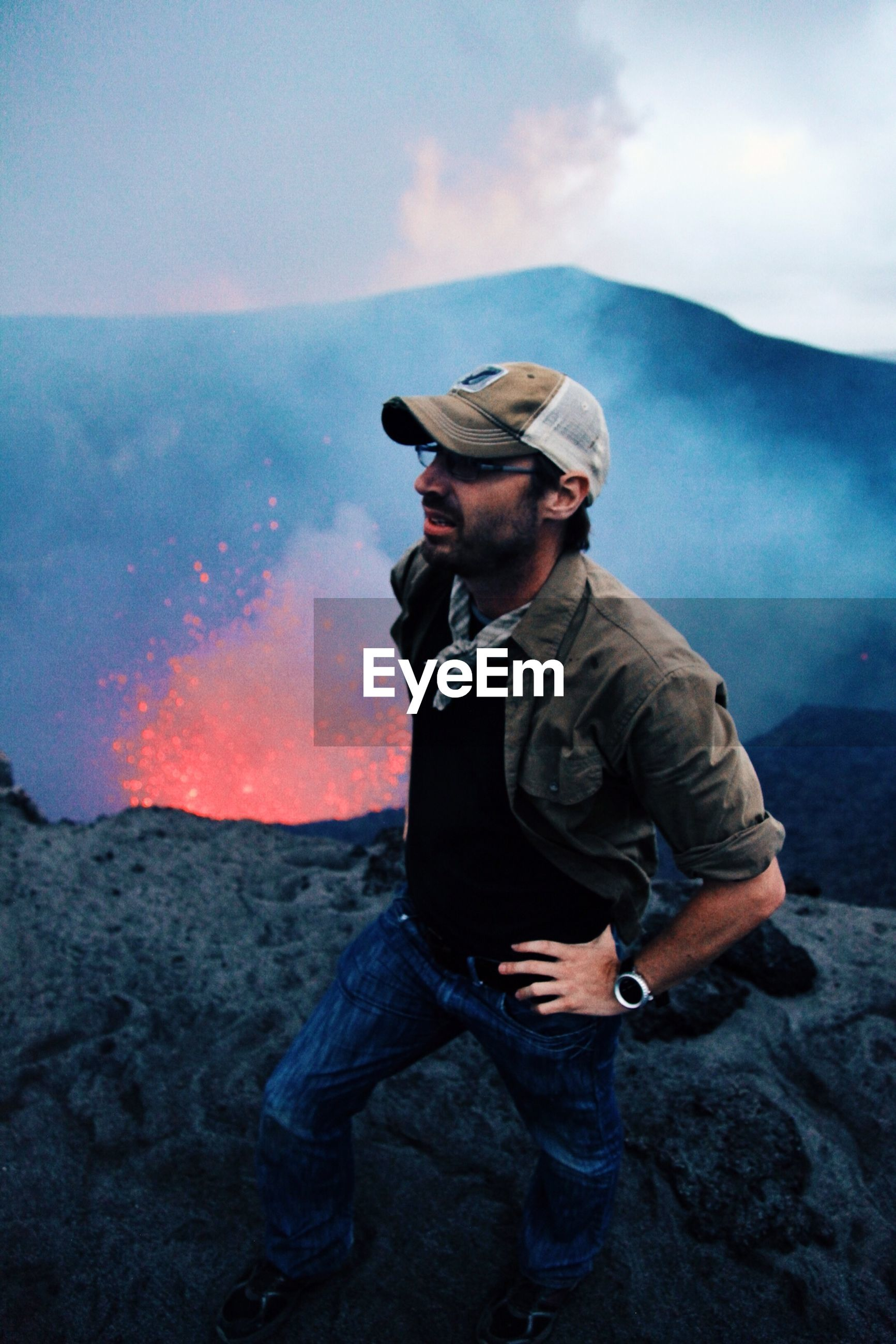 Man standing on rock formation by splashing lava at volcano against sky