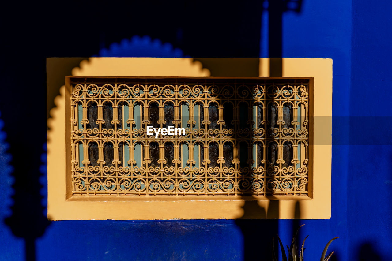 no people, built structure, architecture, blue, window, pattern, building exterior, building, design, close-up, wall - building feature, shadow, sunlight, low angle view, outdoors, illuminated, geometric shape, yellow, shape, architecture and art