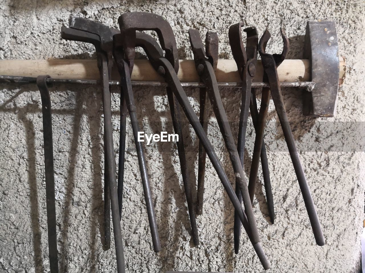 no people, metal, close-up, wall - building feature, work tool, still life, tool, side by side, hand tool, day, wall, choice, variation, equipment, group of objects, outdoors, hanging, rusty, high angle view, old, stone wall, spanner, concrete