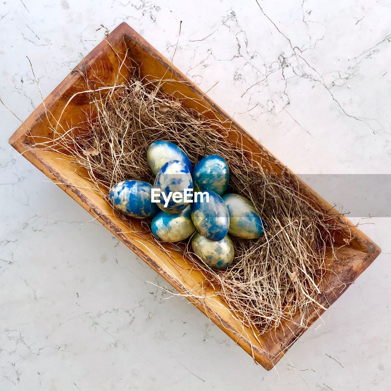 Directly above shot of easter eggs and hay in container on table
