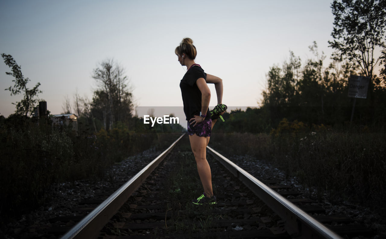 railroad track, one person, track, rail transportation, real people, tree, full length, plant, nature, sky, lifestyles, leisure activity, standing, day, outdoors, clothing, women, holding, shorts