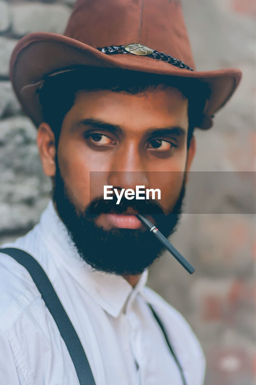 real people, one person, young adult, smoking issues, headshot, focus on foreground, portrait, looking at camera, young men, smoking - activity, front view, lifestyles, close-up, bad habit, leisure activity, cigar, indoors, day