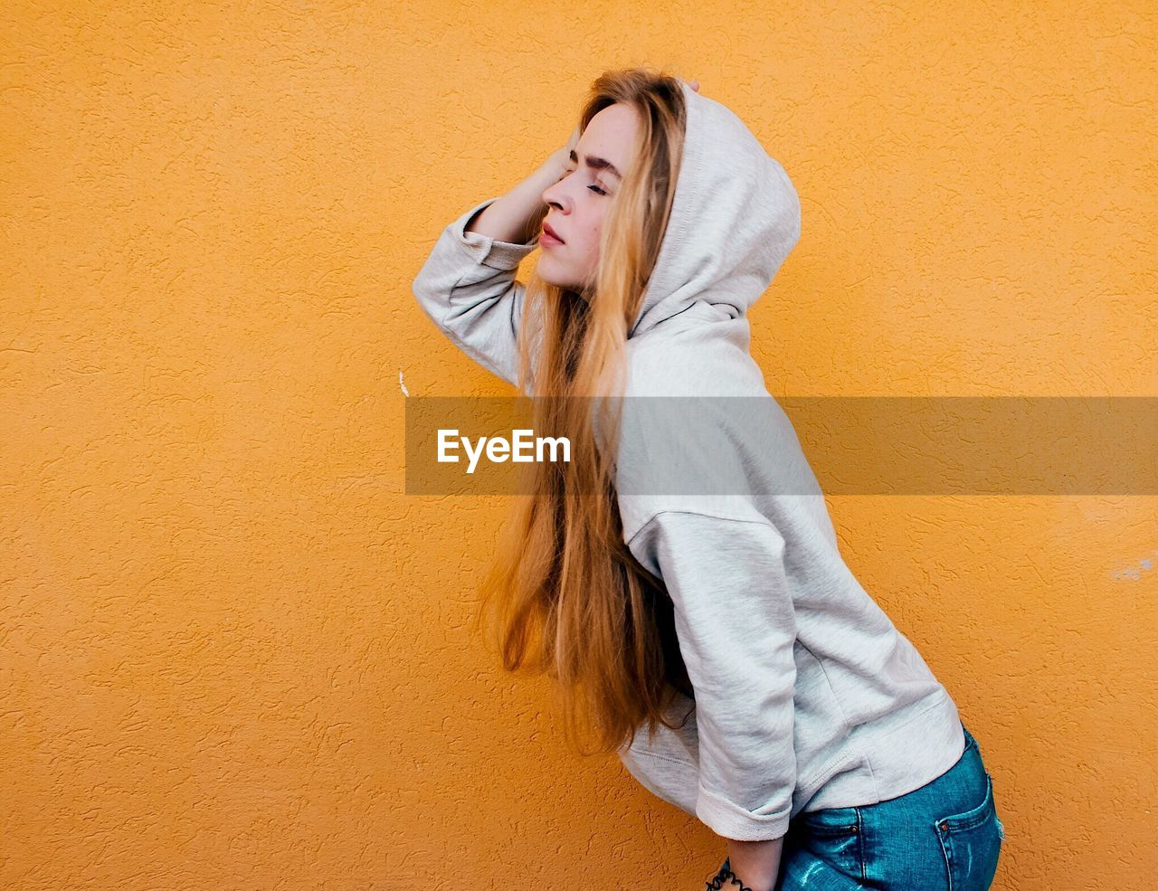 Young Woman In Hood Standing Against Yellow Wall
