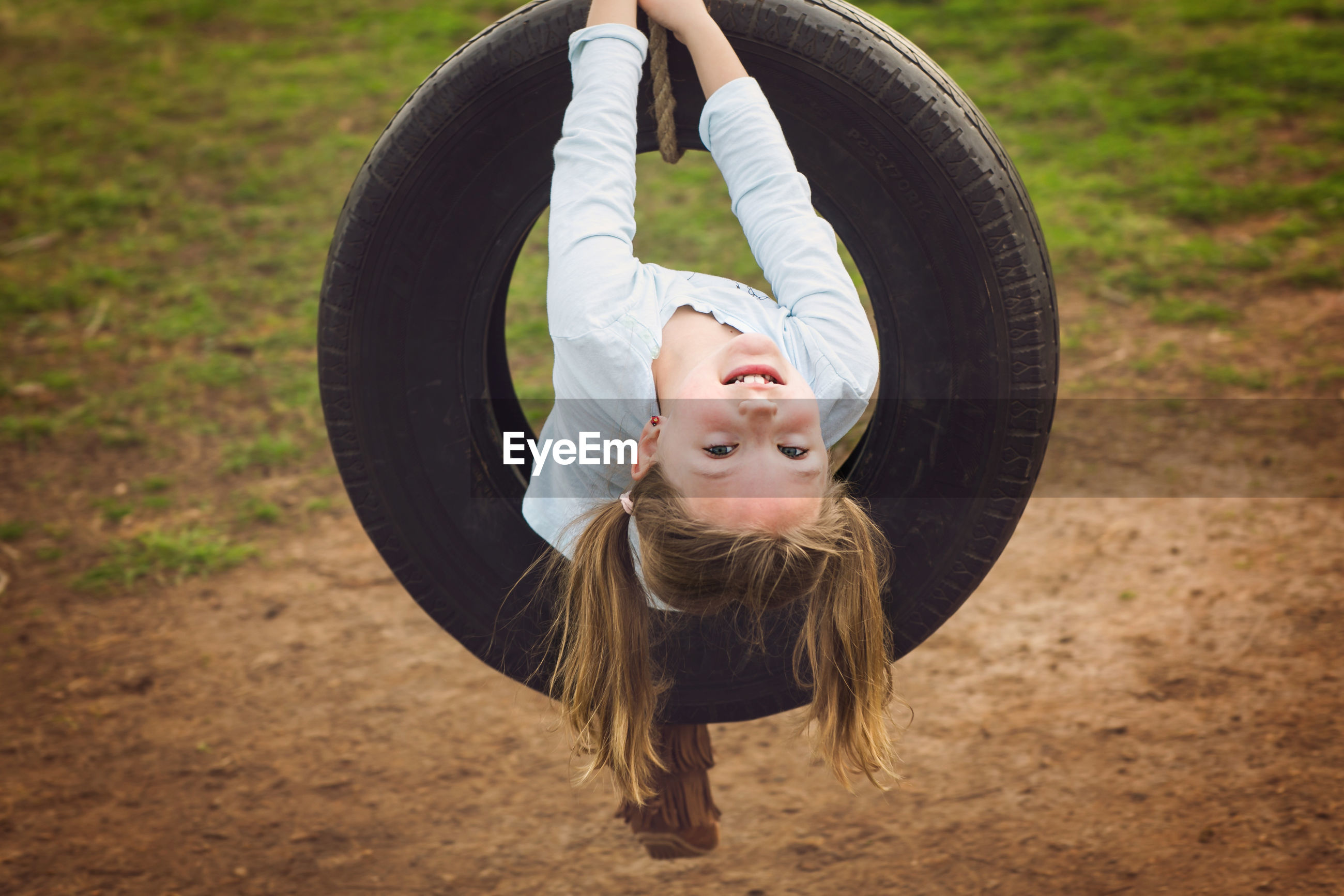 Portrait of cute girl playing with tire swing in playground