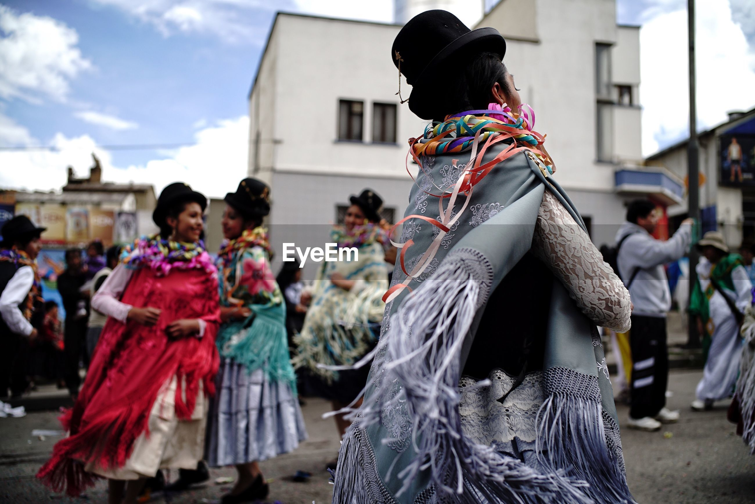 People in traditional costumes dancing during celebration in city