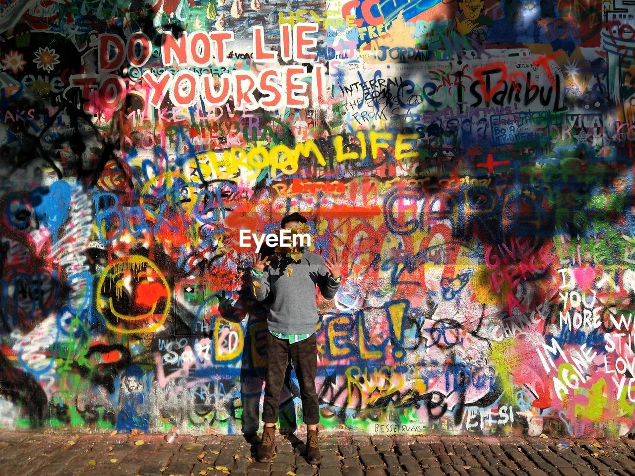 multi colored, graffiti, creativity, city, text, full length, architecture, art and craft, one person, communication, street art, western script, wall - building feature, street, adult, day, paint, standing, motion, outdoors, obscured face