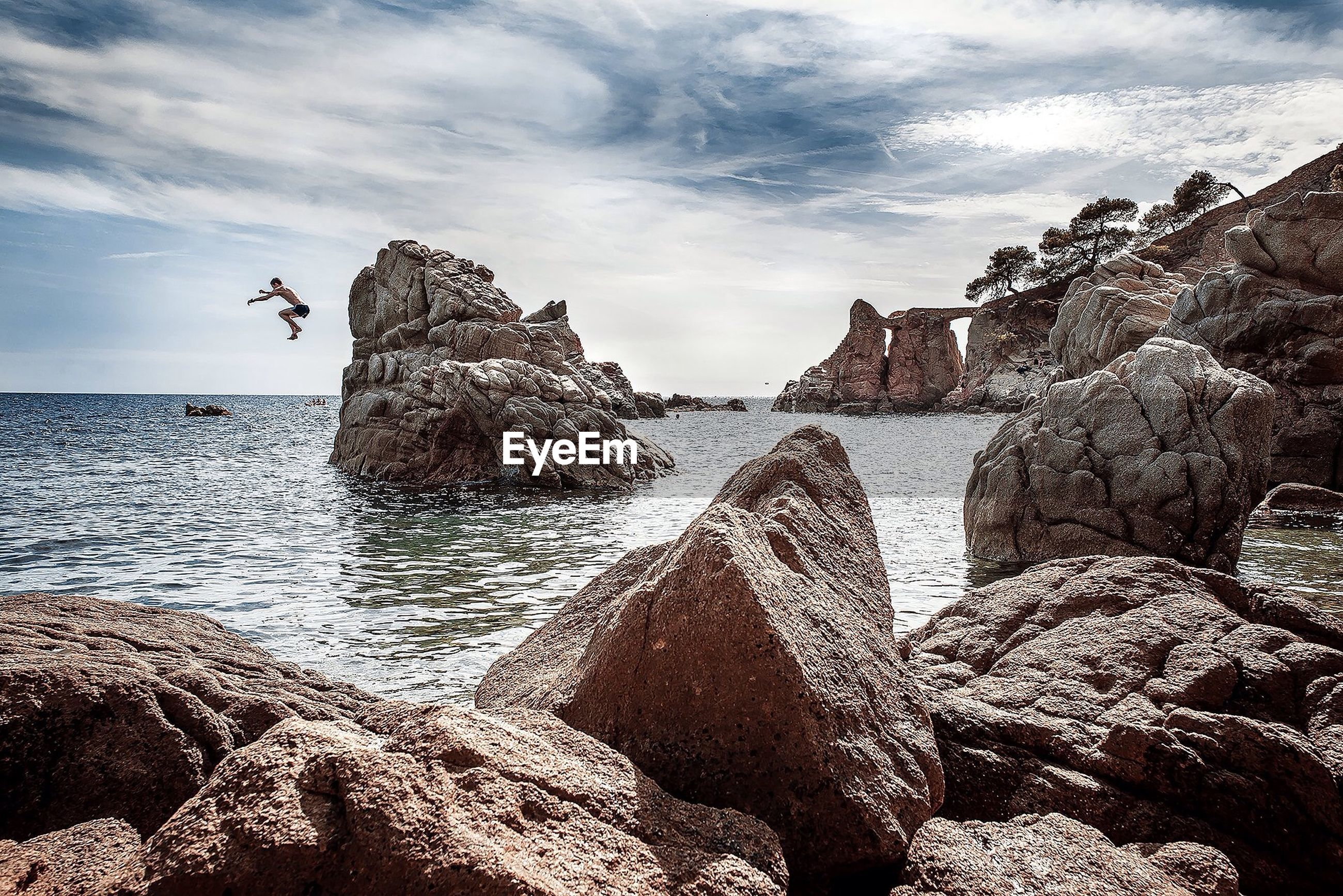 Young man jumping from rock into sea