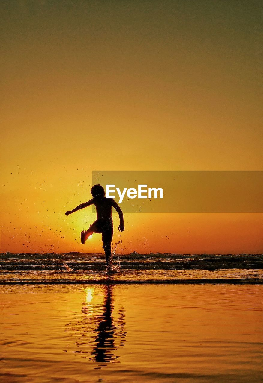 Rear view of silhouette boy enjoying on sea shore against sky during sunset