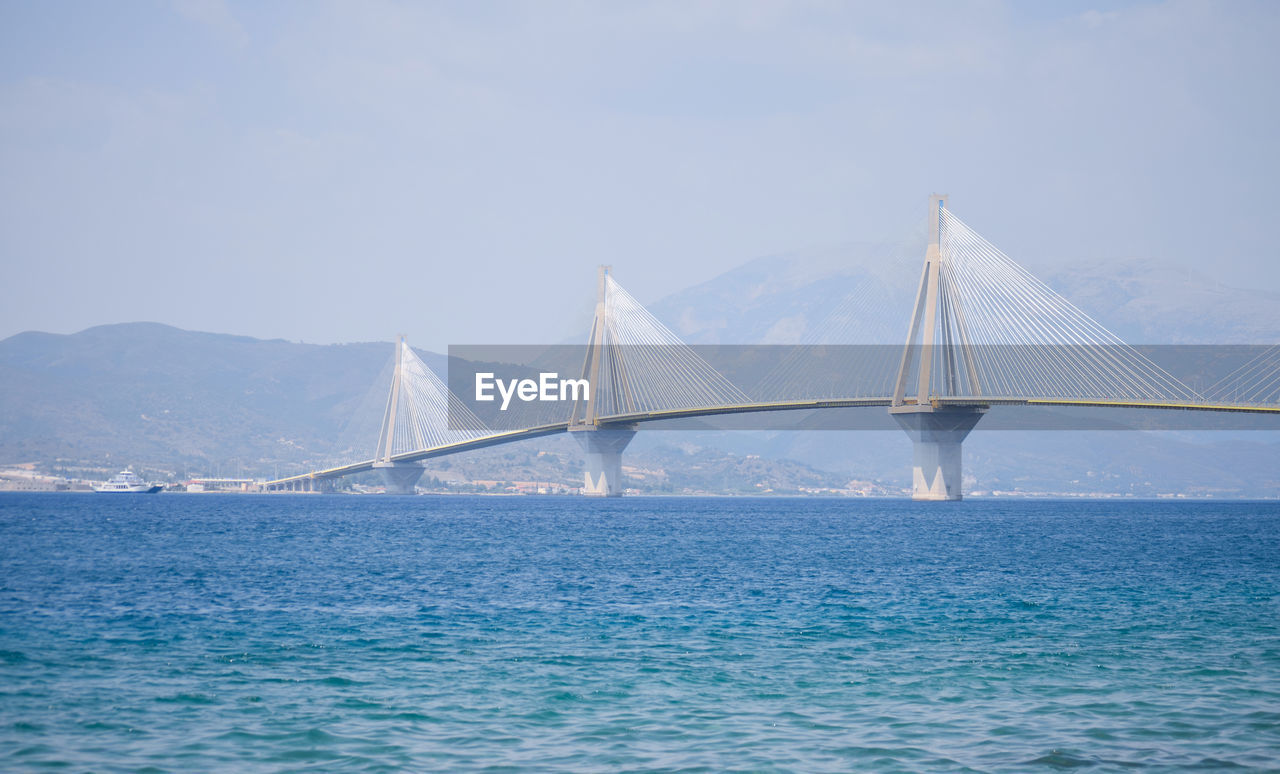 Cable-stayed bridge over bay against clear sky