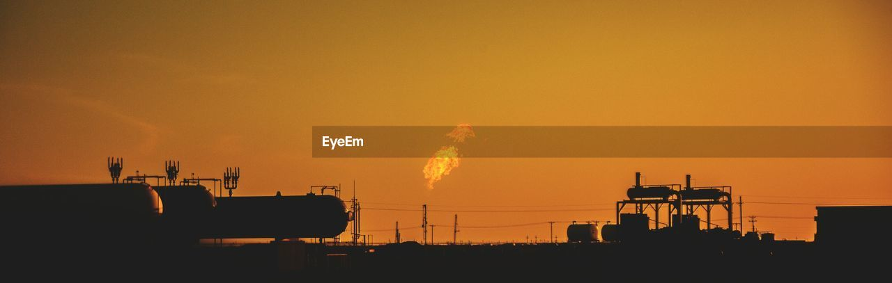 Silhouette Smoke Emitting From Factory Against Sky During Sunset