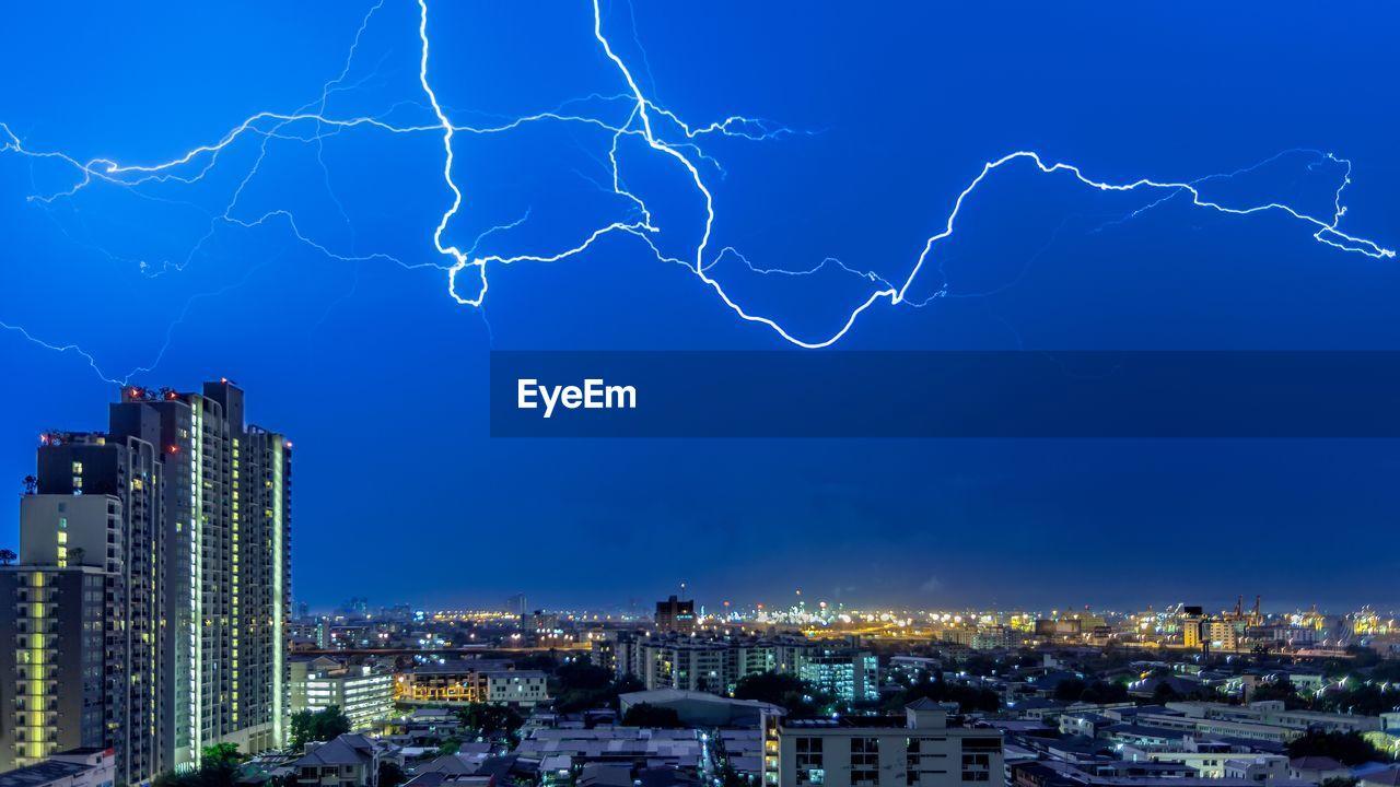 Lightning in city against sky at night