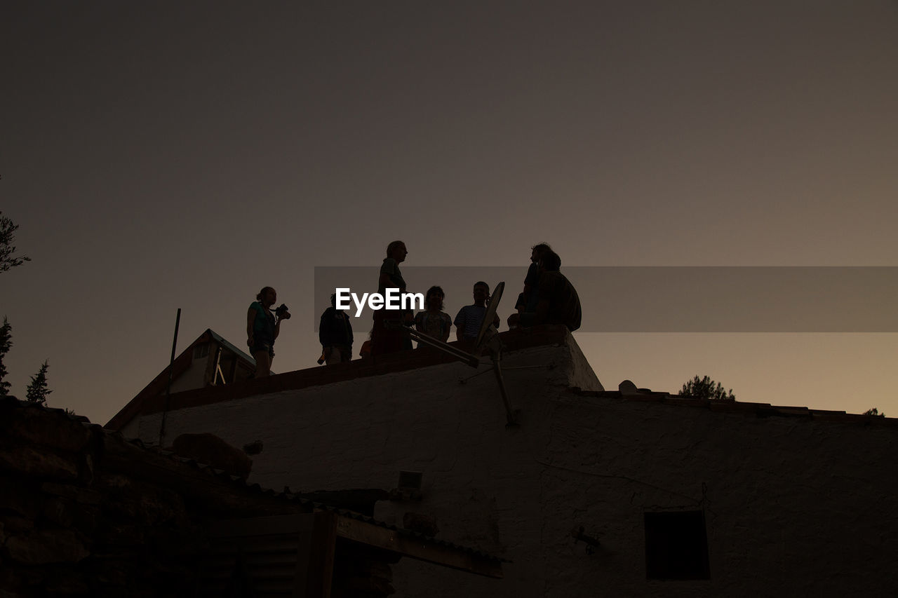 low angle view, clear sky, copy space, built structure, outdoors, silhouette, sunset, architecture, real people, sky, roof, nature, large group of people, day, men, building exterior, people