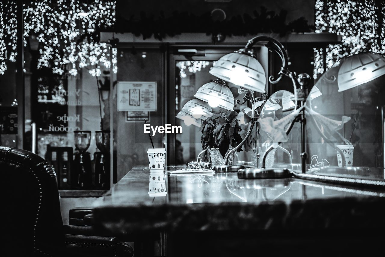 selective focus, glass - material, no people, reflection, transparent, business, store, indoors, for sale, retail, choice, representation, night, illuminated, shopping, table, still life, restaurant, human representation