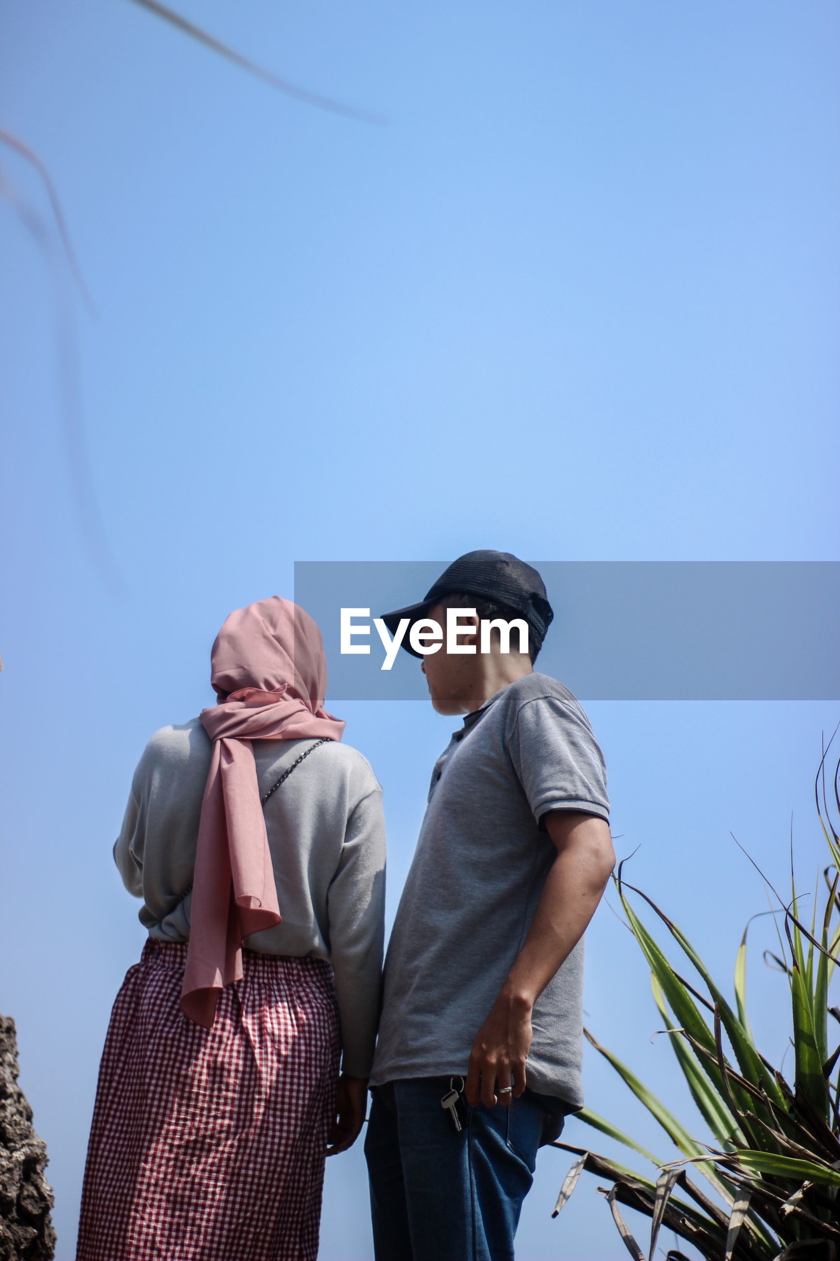 Low angle view of couple standing against clear sky