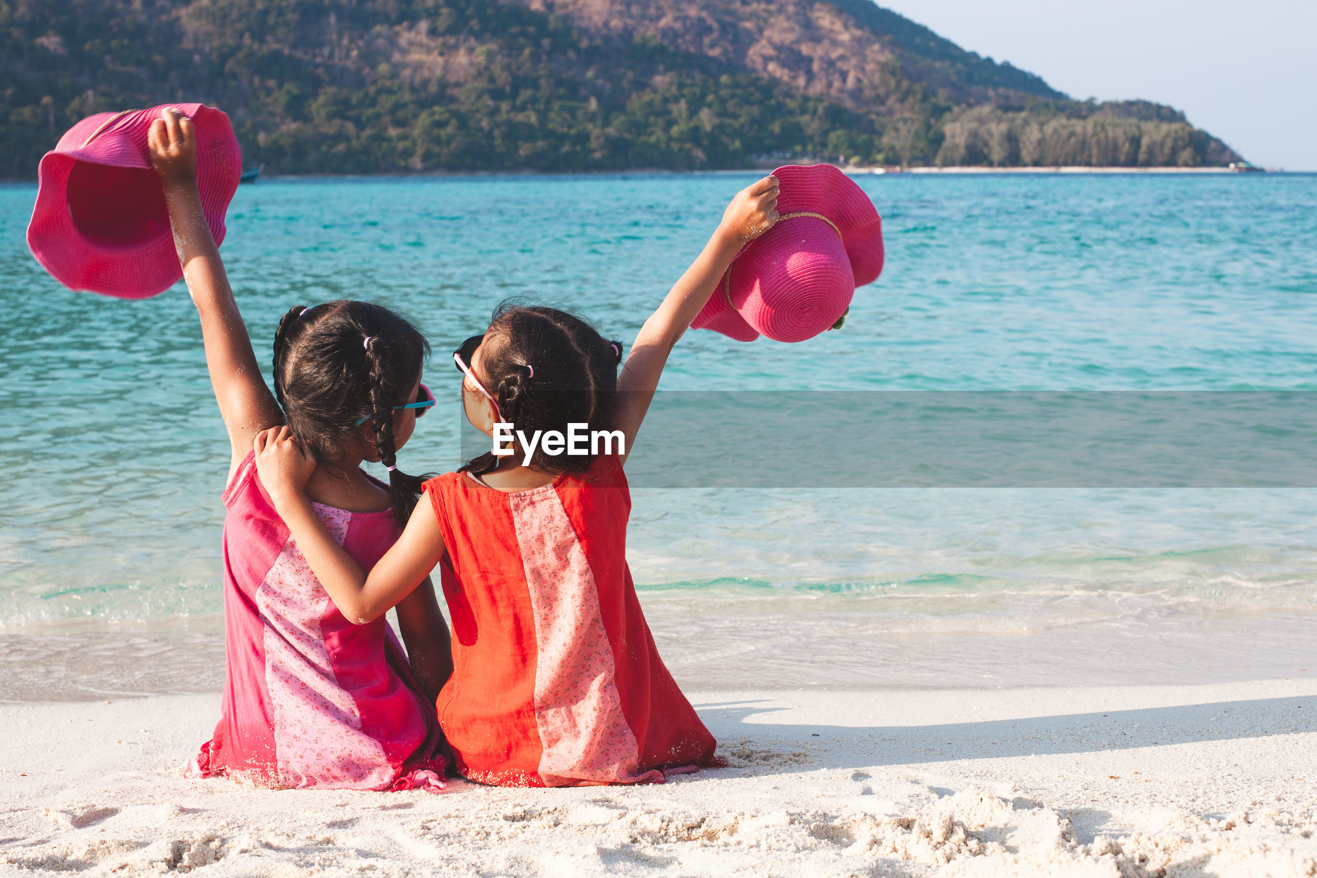 Rear view of siblings sitting at beach against clear sky