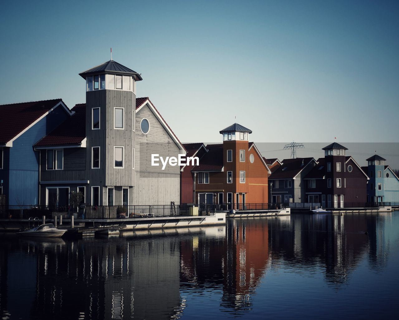 built structure, architecture, building exterior, building, water, sky, waterfront, reflection, house, no people, residential district, nature, clear sky, outdoors, city, river, day, blue, row house