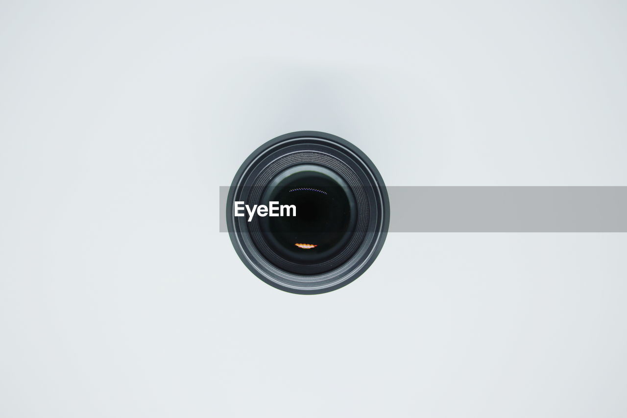 Directly above shot of camera lens on white background