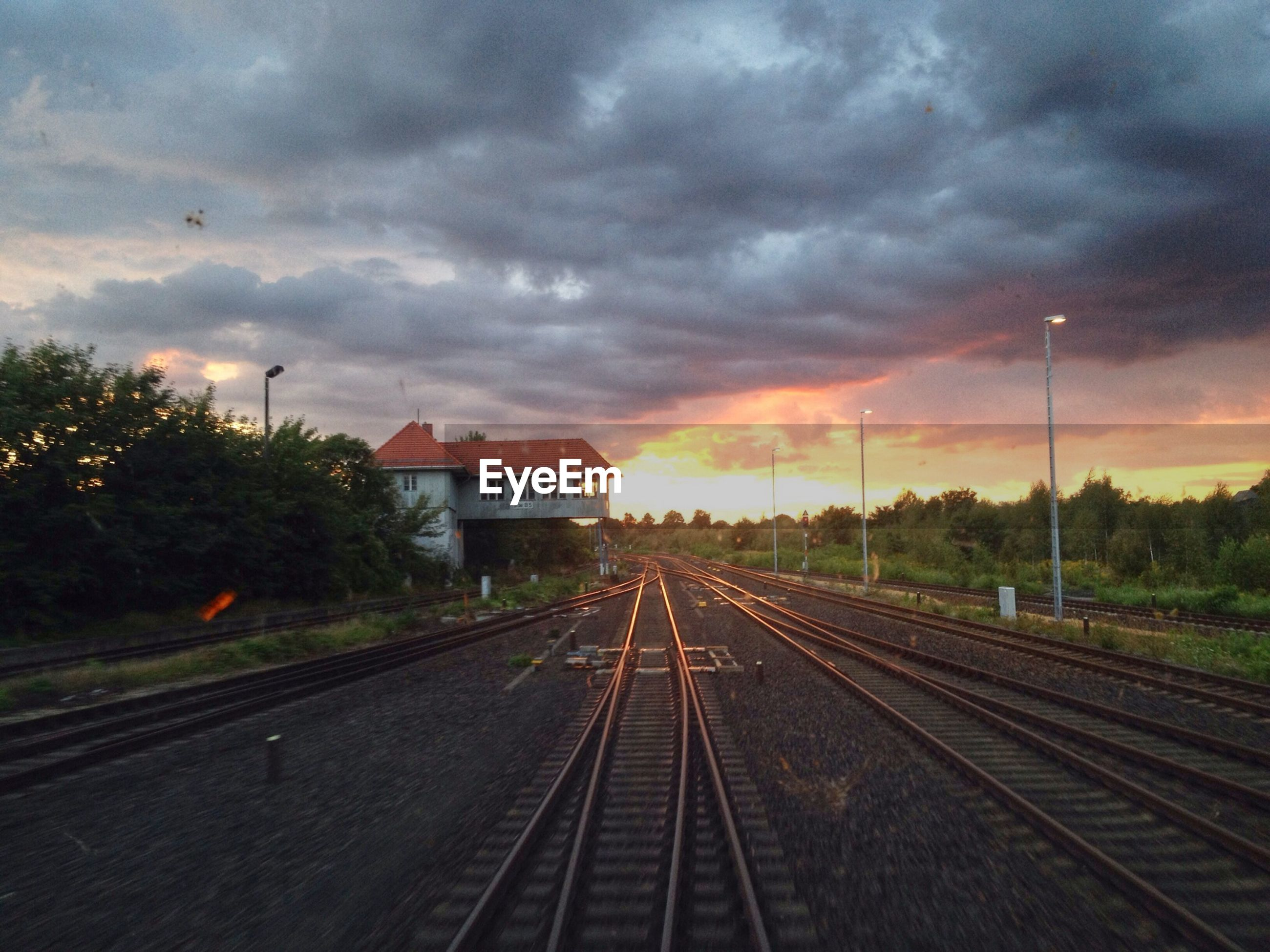 Railroad tracks against cloudy sky during sunset