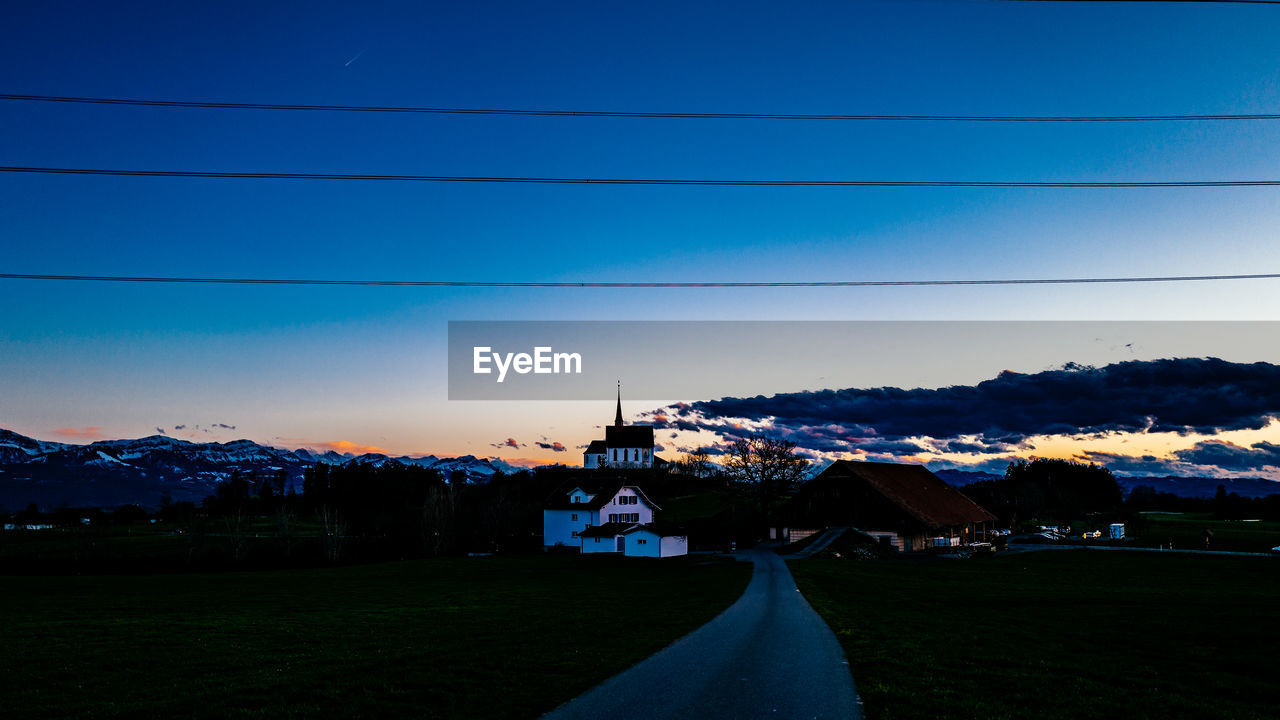 cable, building exterior, built structure, architecture, power line, sky, outdoors, blue, nature, electricity pylon, house, no people, power supply, town, scenics, beauty in nature, landscape, tree, sunset, mountain, clear sky, day, telephone line