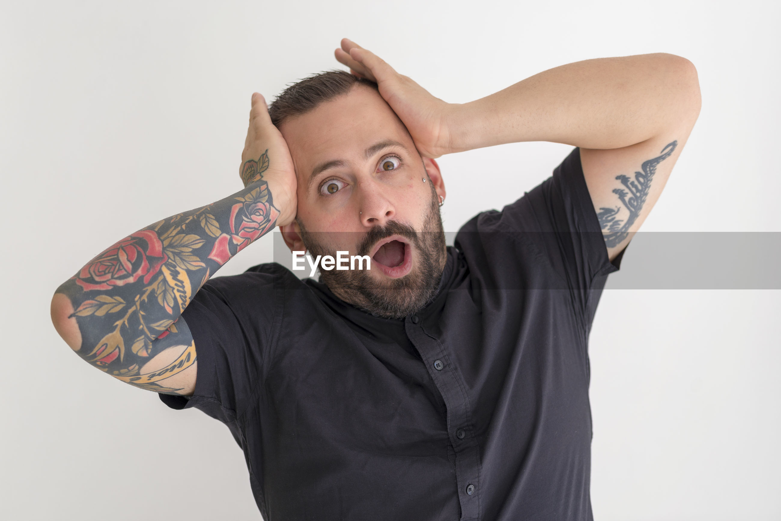 Portrait of shocked man standing against white background