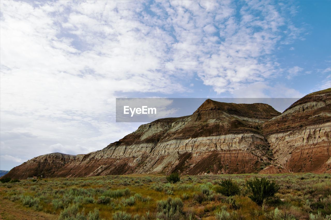sky, cloud - sky, mountain, scenics - nature, tranquil scene, non-urban scene, beauty in nature, day, nature, no people, tranquility, land, rock, plant, landscape, environment, rock - object, rock formation, grass, solid, mountain range, outdoors, formation, arid climate, eroded