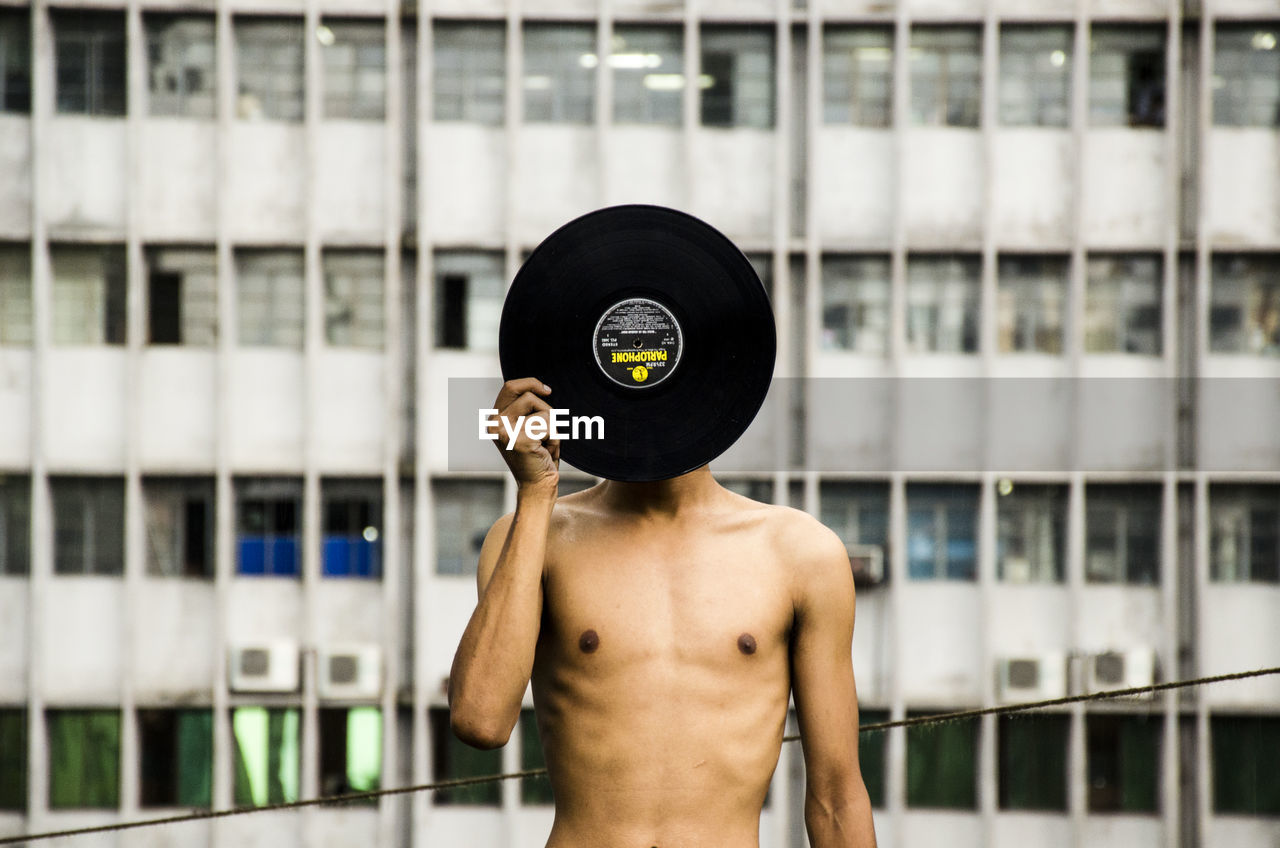 Shirtless man covering his face with record against building