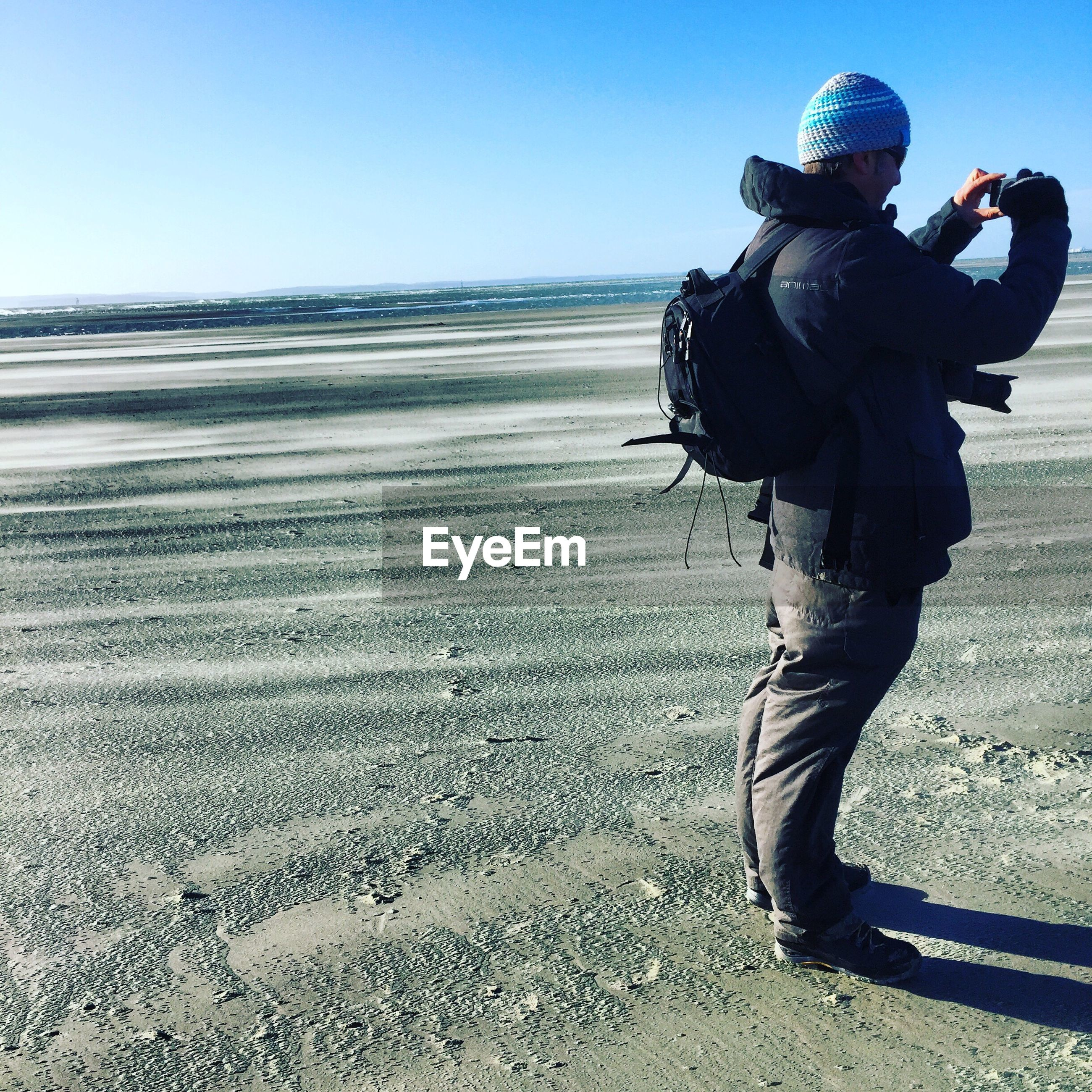 Full length of man photographing at beach against clear sky