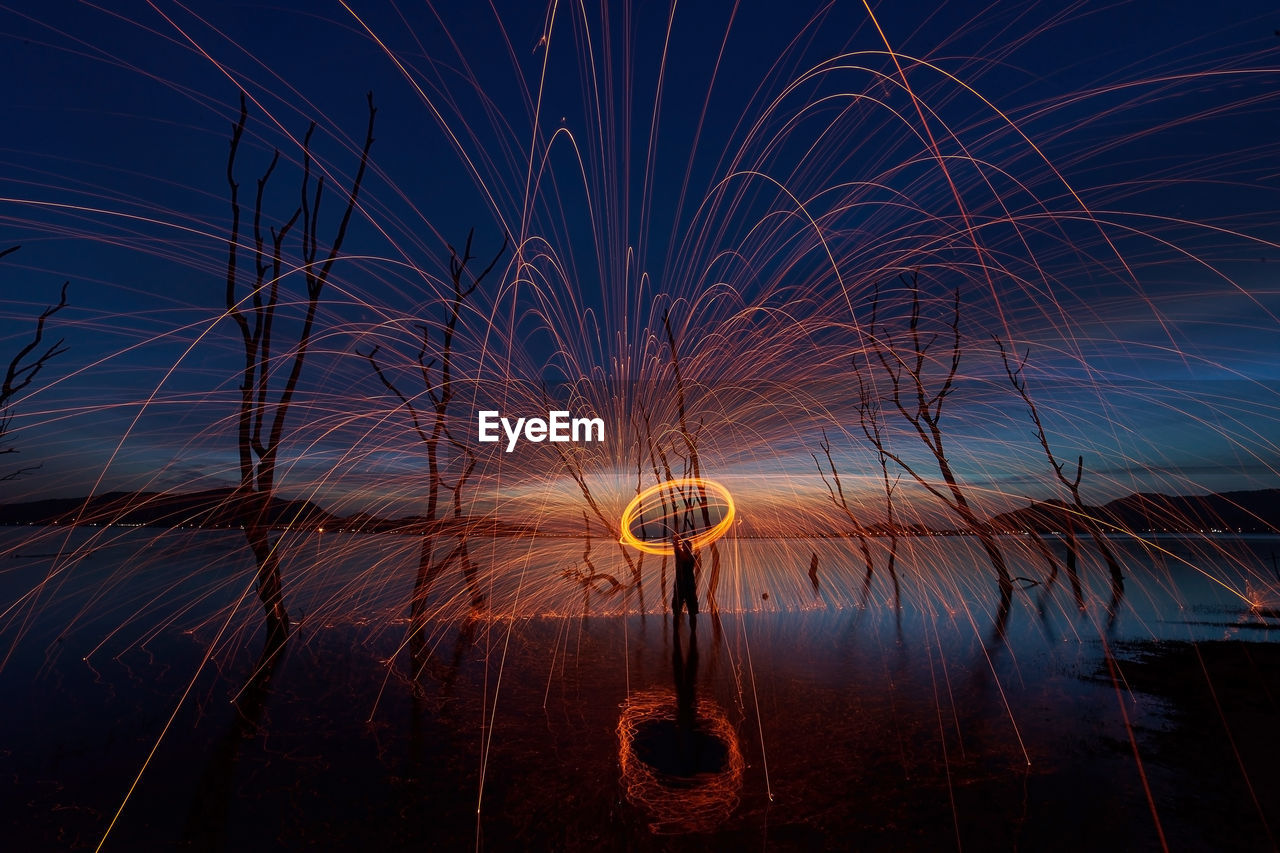 Silhouette man spinning wire wool against sky during dusk
