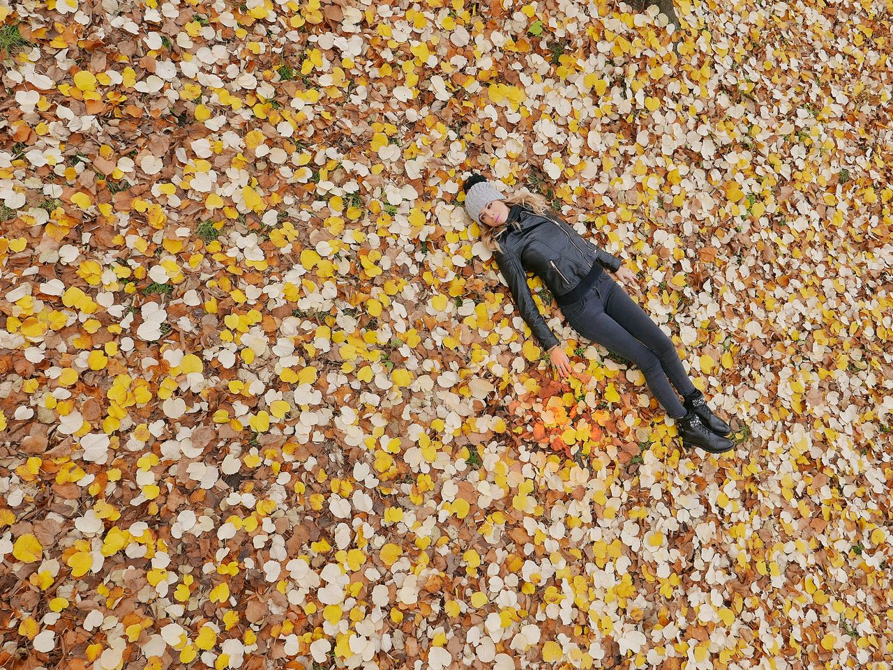 High angle view of woman lying on field during autumn