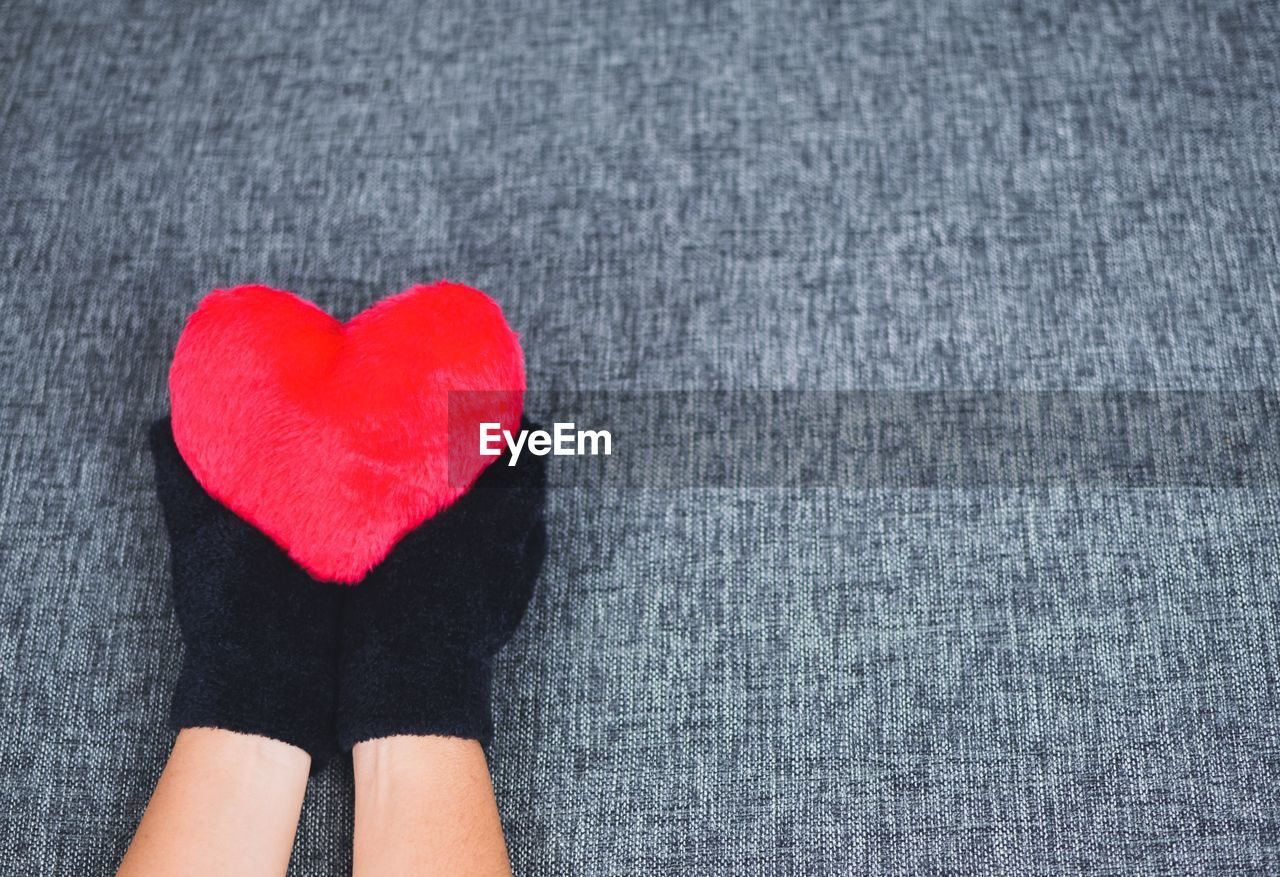 Cropped Hands Of Person Holding Red Heart Shape On Table