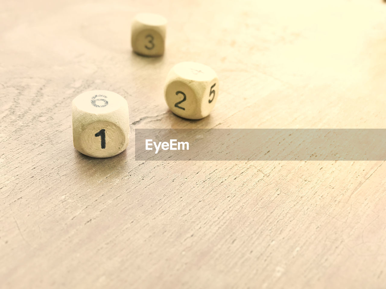 table, still life, dice, indoors, wood - material, number, no people, close-up, relaxation, leisure games, leisure activity, selective focus, arts culture and entertainment, high angle view, cube shape, geometric shape, design, shape, letter, group of objects
