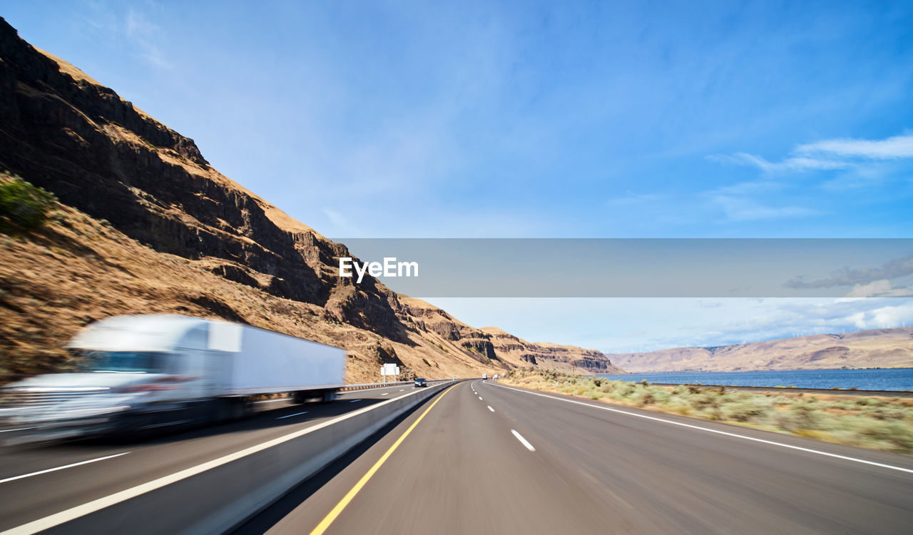 transportation, road, sky, mountain, land vehicle, mode of transportation, symbol, motion, cloud - sky, motor vehicle, car, nature, marking, road marking, no people, the way forward, sign, day, direction, beauty in nature, mountain range, diminishing perspective, outdoors, dividing line, road trip