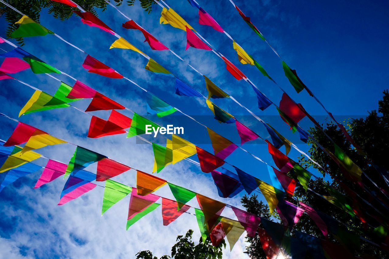 sky, multi colored, low angle view, flag, blue, decoration, nature, no people, built structure, cloud - sky, architecture, day, building exterior, celebration, outdoors, hanging, bunting, building, tree, plant, festival