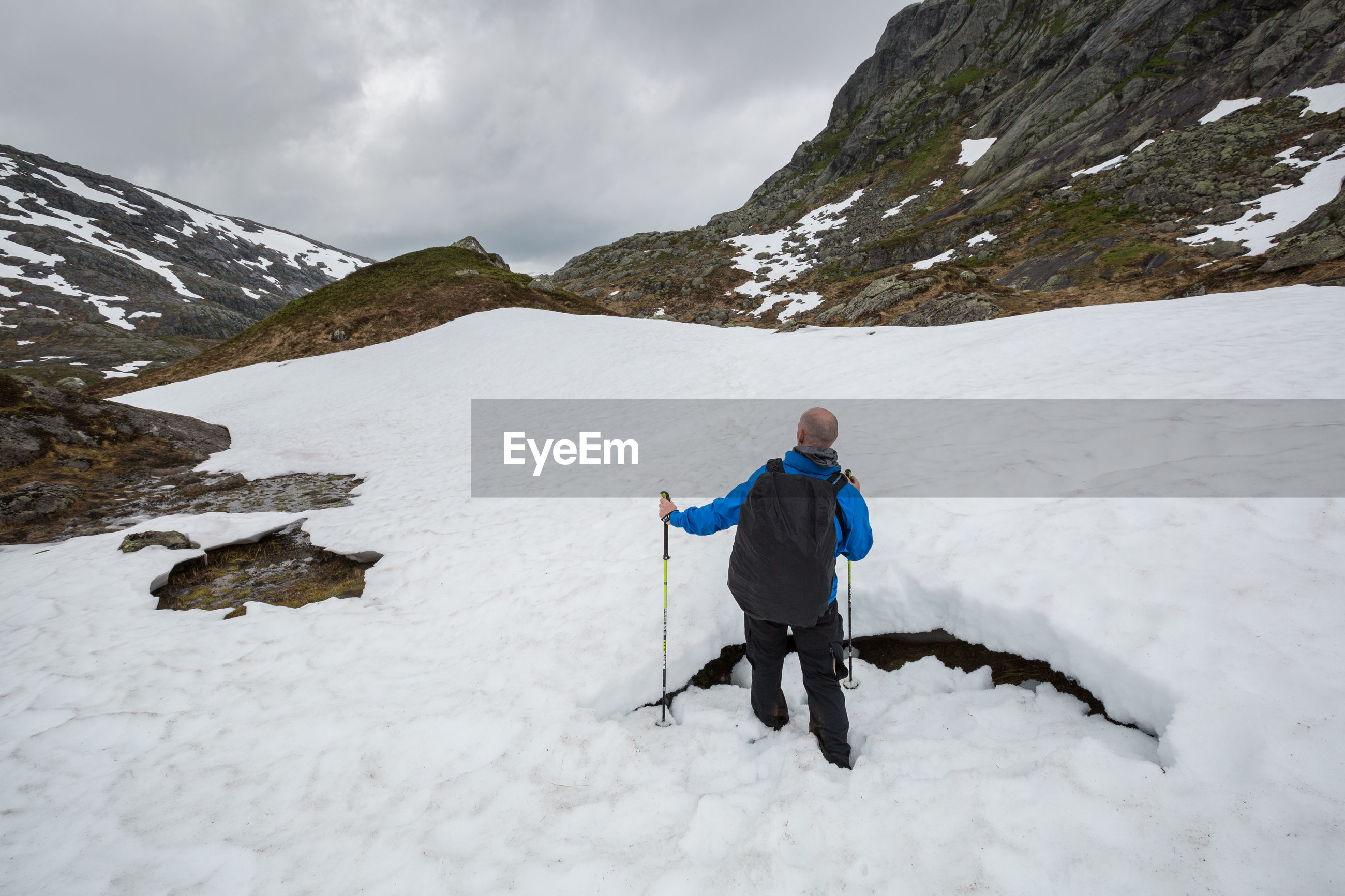 Rear view of hiker walking on snow covered field by rocky mountains against sky