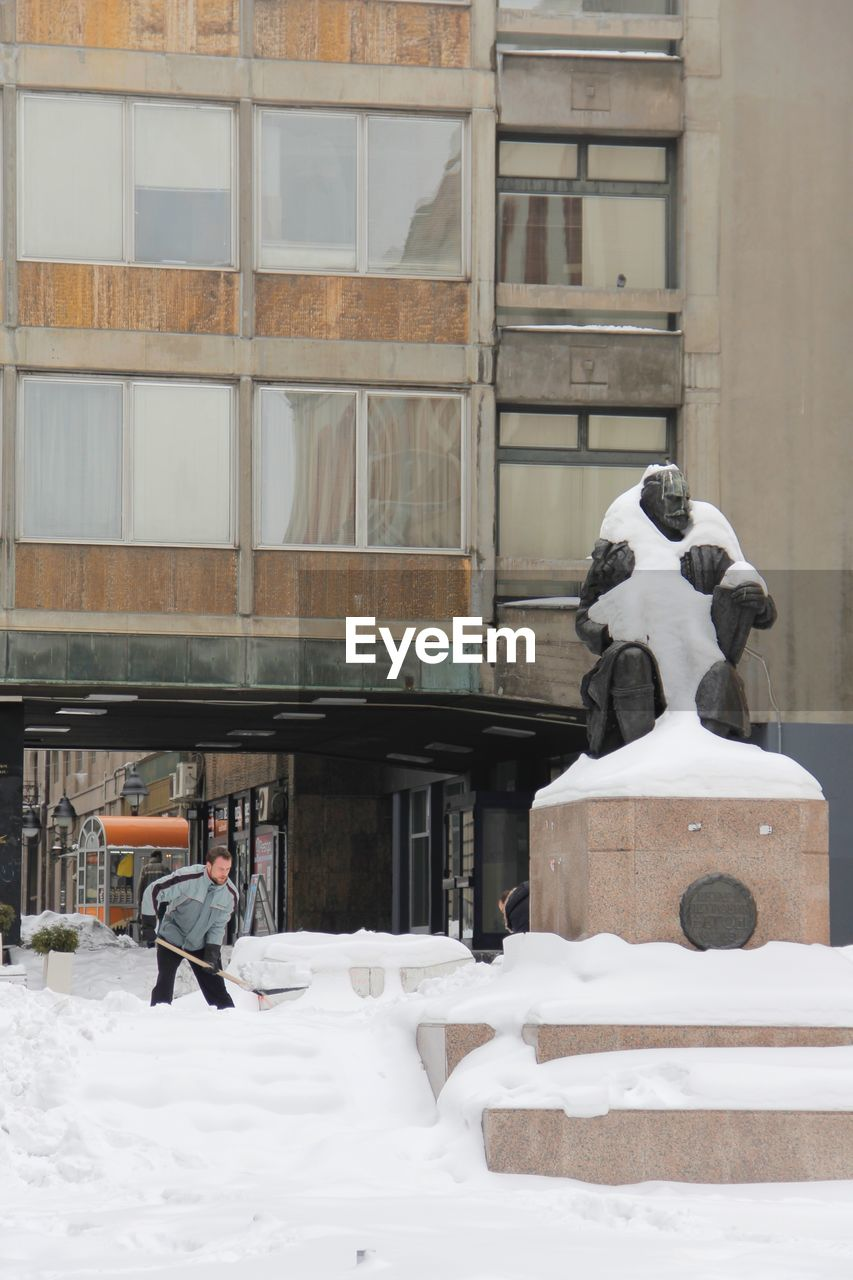 architecture, built structure, building exterior, representation, human representation, snow, day, art and craft, building, creativity, winter, sculpture, cold temperature, male likeness, statue, white color, window, outdoors, nature, snowing