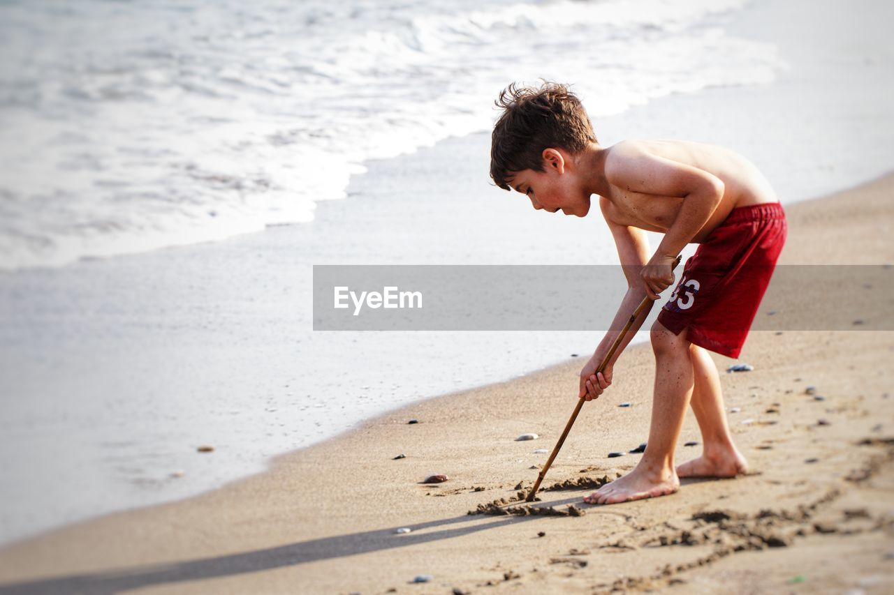 Side View Of Shirtless Boy Playing With Sand At Beach