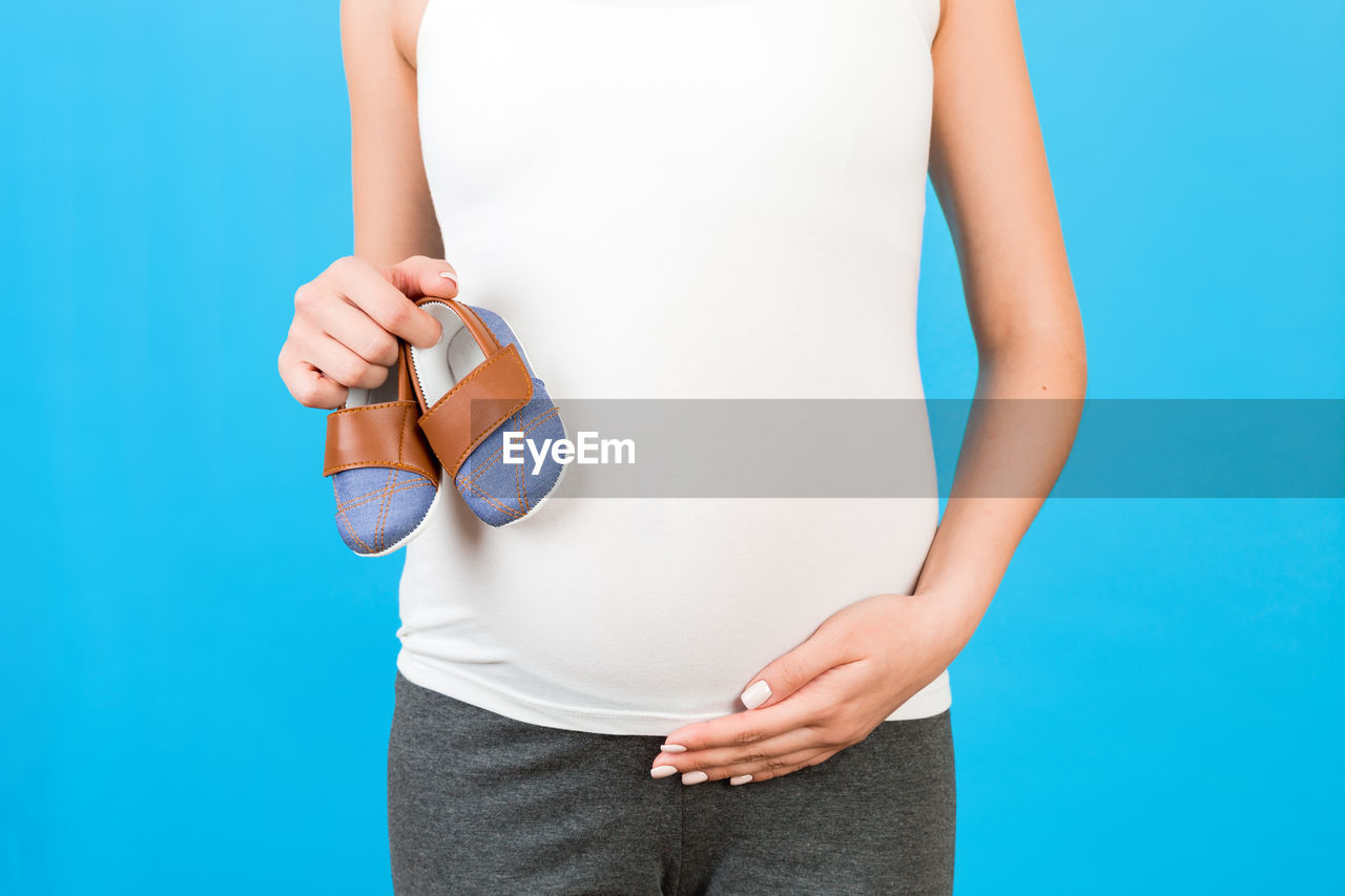 MIDSECTION OF WOMAN HOLDING BLUE WHILE STANDING AGAINST GRAY BACKGROUND