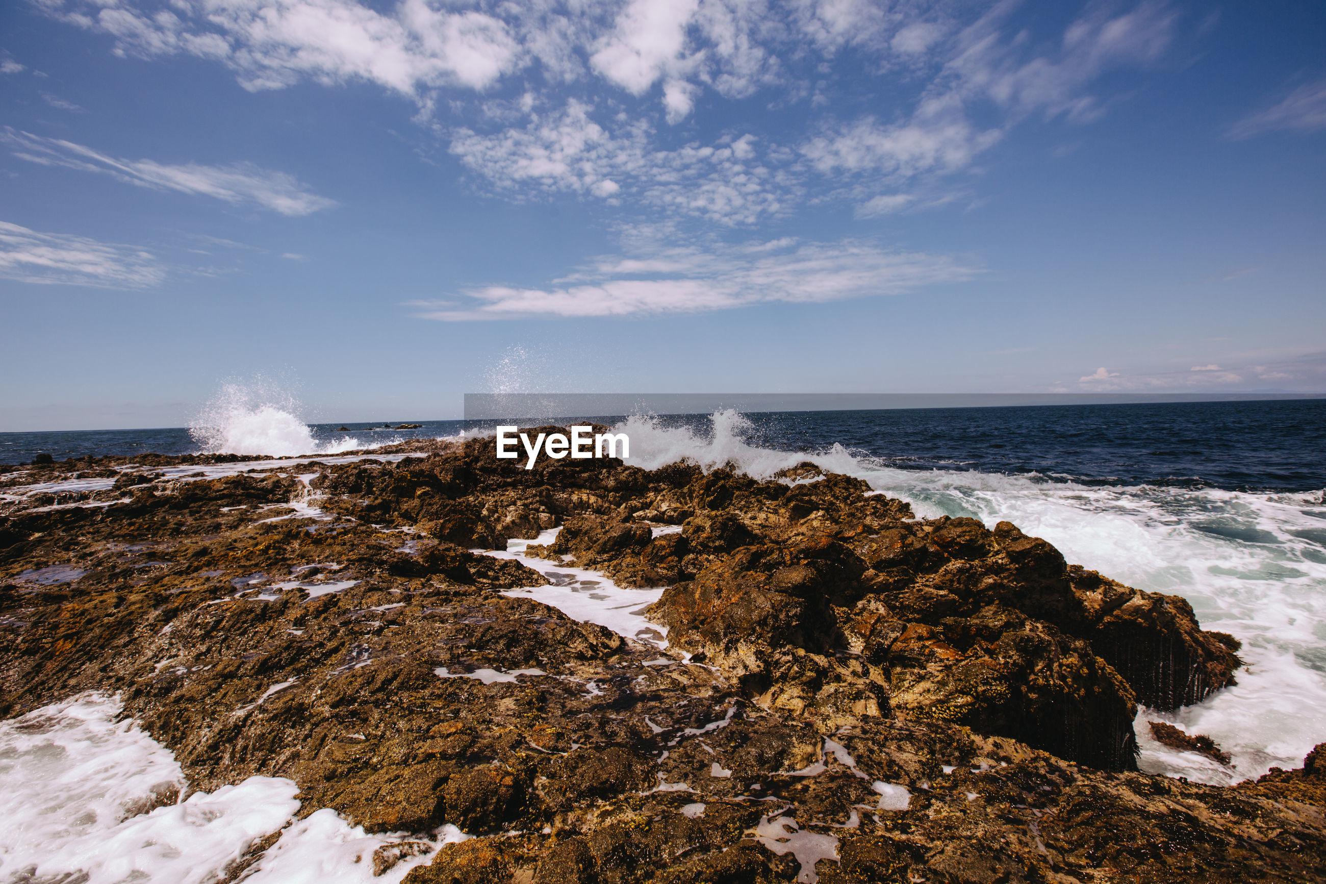 A blue sky, and crashing waves