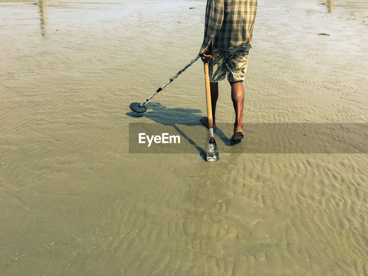 Low section of man holding tools at beach