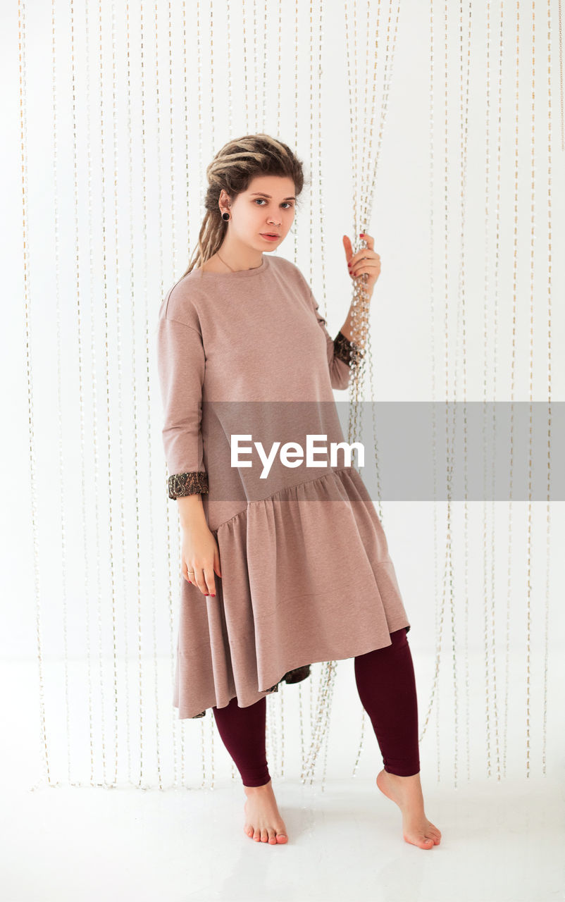 FULL LENGTH PORTRAIT OF WOMAN STANDING AGAINST CURTAIN