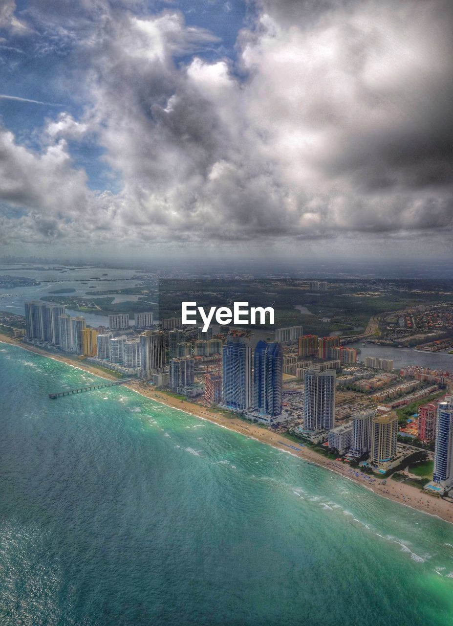 Aerial View Of Sea And Buildings Against Cloudy Sky