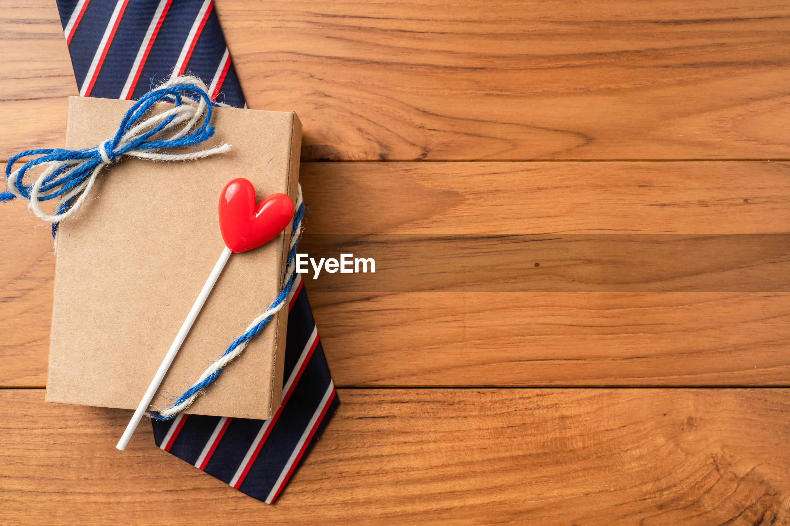 Directly above shot of box with candy and necktie on wooden table