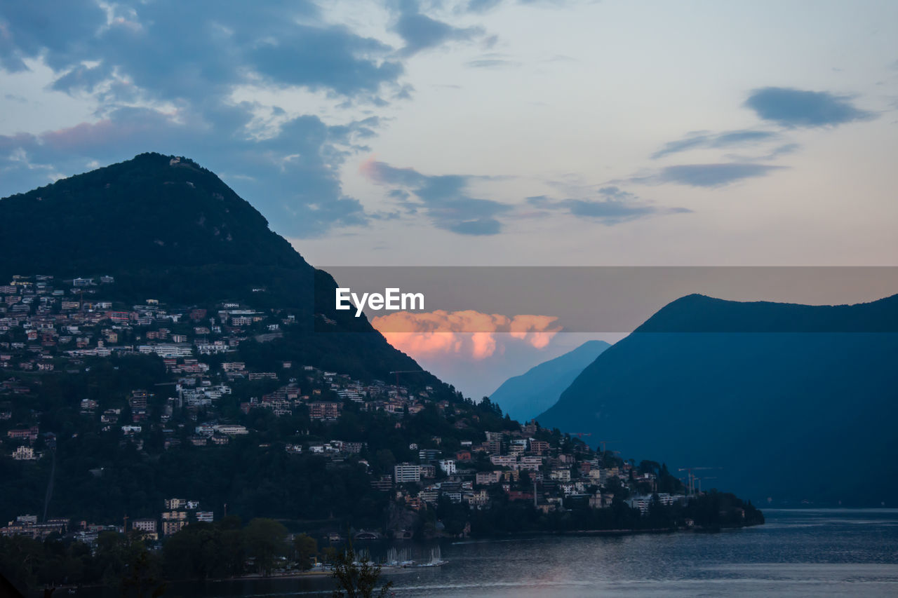 Houses On Mountain By Lake Against Sky During Sunset
