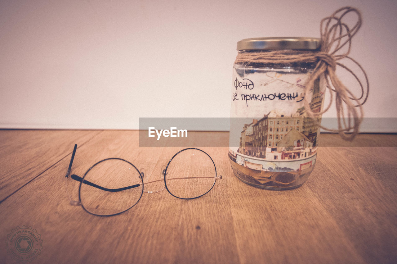 Close-Up Of Eyeglasses By Jar On Wooden Table