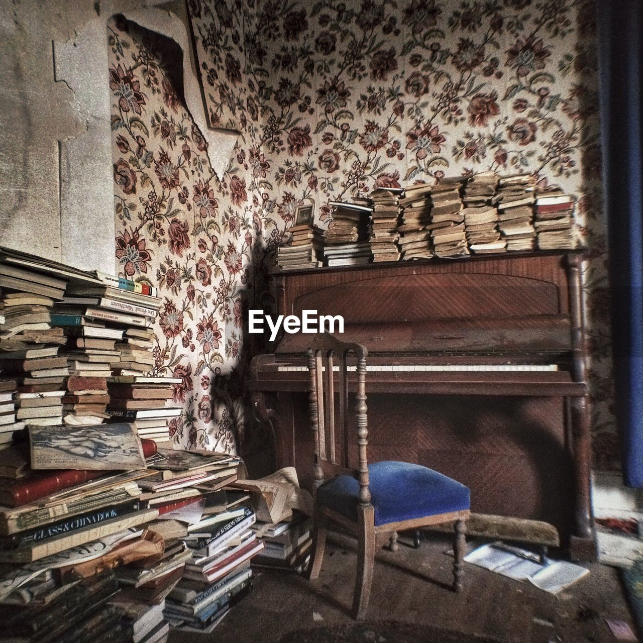 publication, indoors, book, seat, large group of objects, no people, wood - material, stack, chair, absence, table, old, antique, architecture, furniture, shelf, the past, wall - building feature, home interior