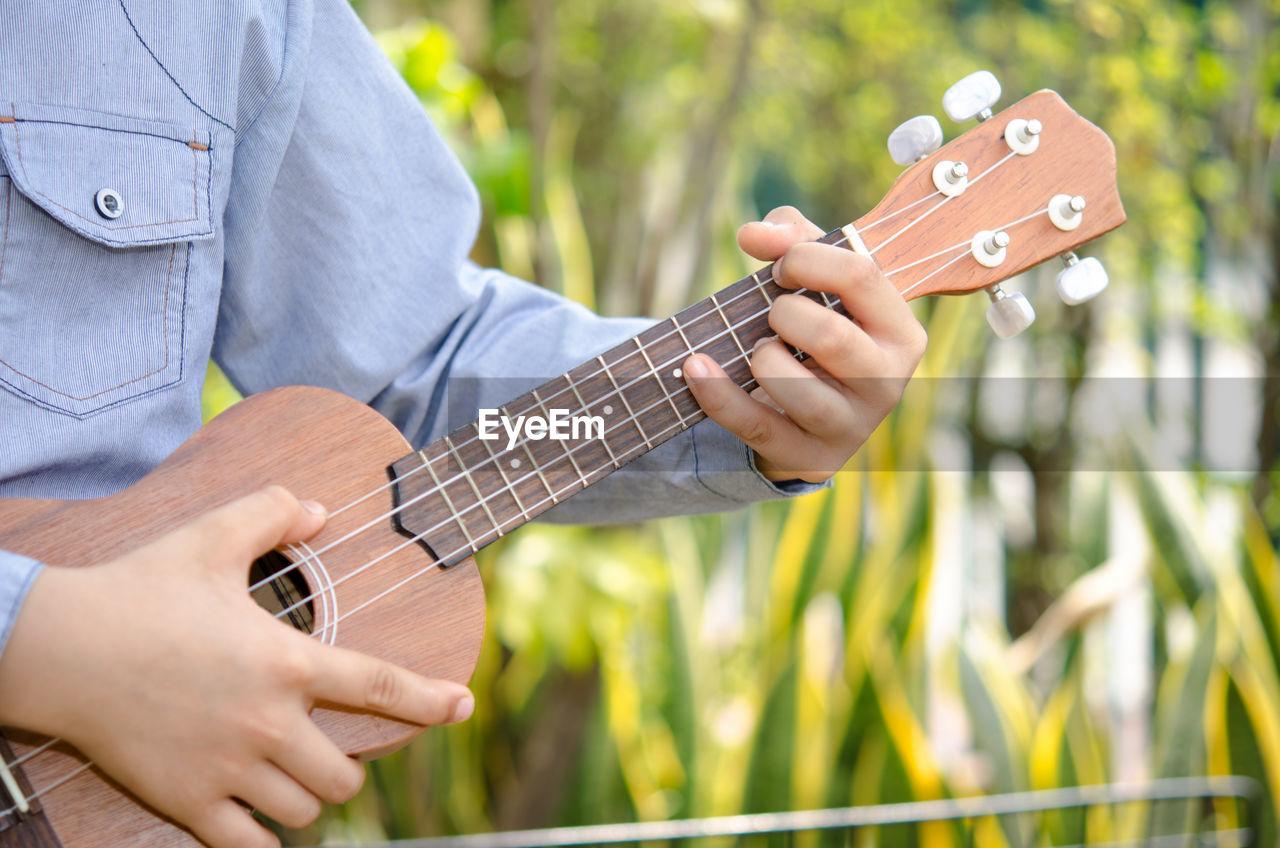 Cropped Image Of Man Playing Guitar In Yard