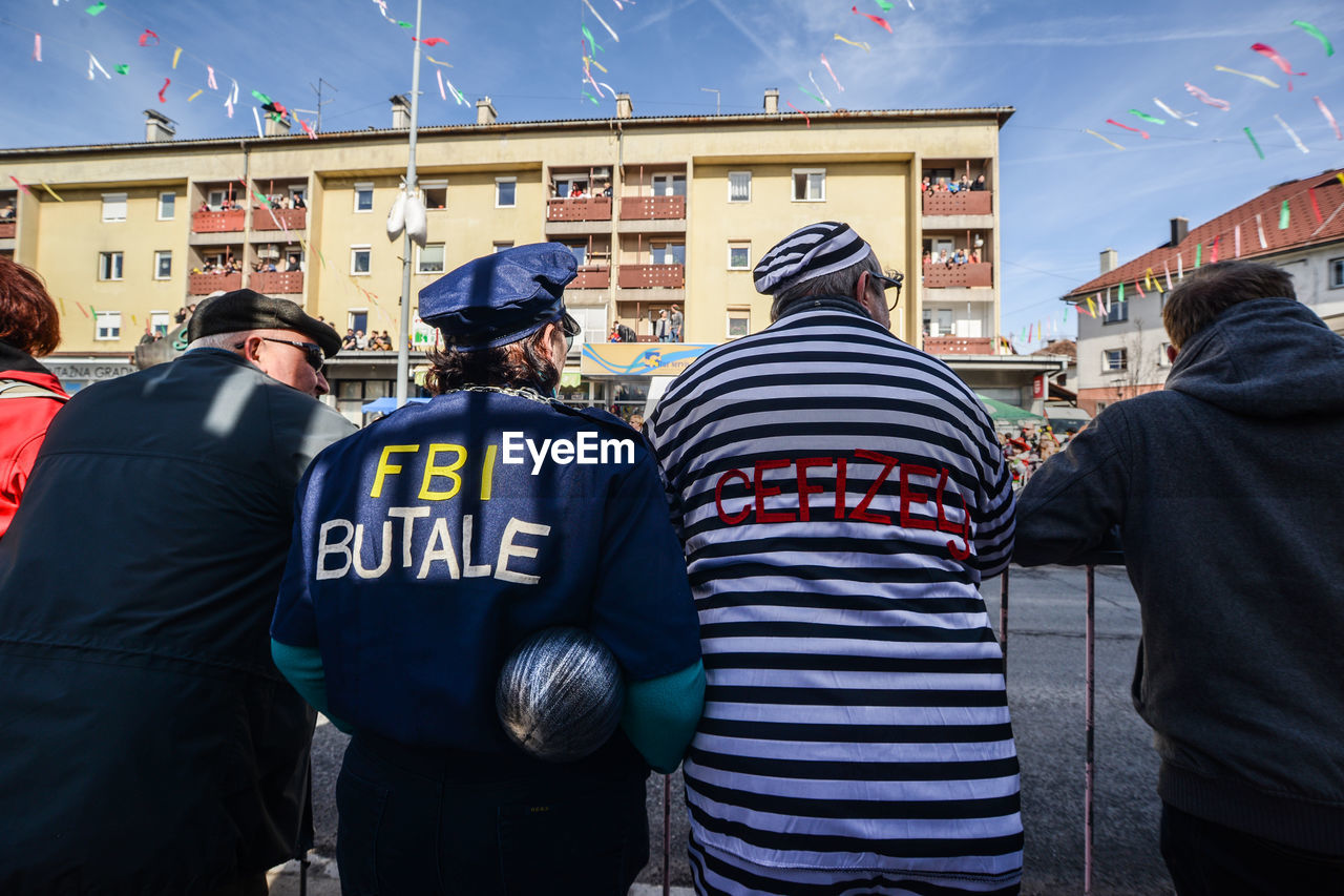 rear view, real people, building exterior, men, built structure, architecture, police force, day, police uniform, outdoors, shield, city, riot